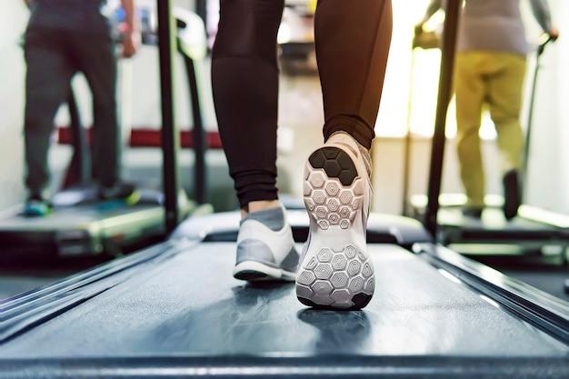 Trainieren sie laufband-cardio-lauftraining im fitness-studio der frau, die gewichtsverlust mit maschinenaerobic für schlank und fest und gesund am morgen nimmt. konzept des laufens und des sports. laufende sportler.
