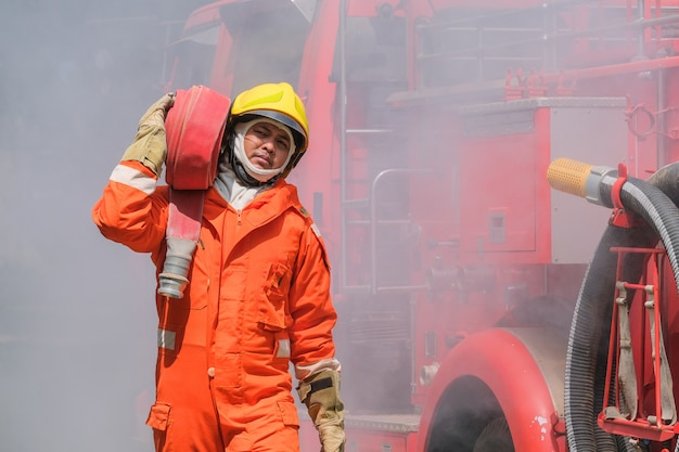 Training der feuerwehrmänner, teamübungen zur brandbekämpfung in notsituationen. ein feuerwehrmann trägt einen wasserschlauch durch die flamme