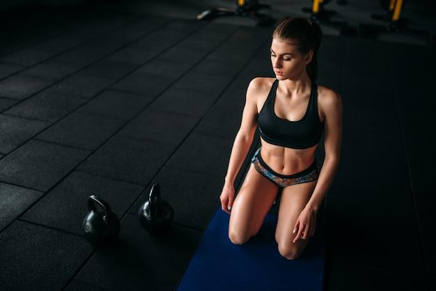 Training der jungen frau im fitnessclub. sportlerin in sporthalle. attraktives mädchen auf fit-training