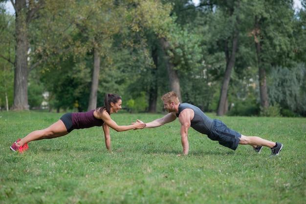 Training der jungen frau mit ihrem persönlichen trainer im park