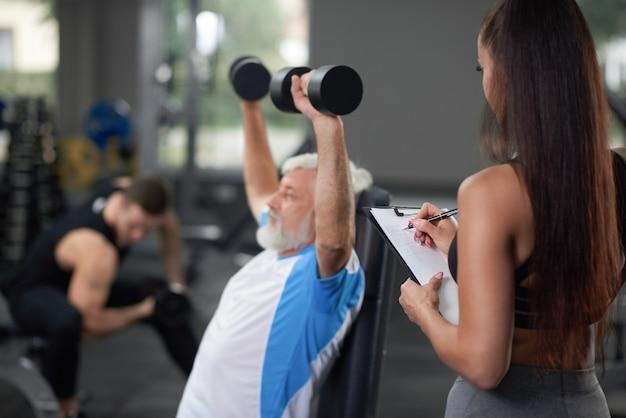 Training des älteren mannes mit frau in der turnhalle.