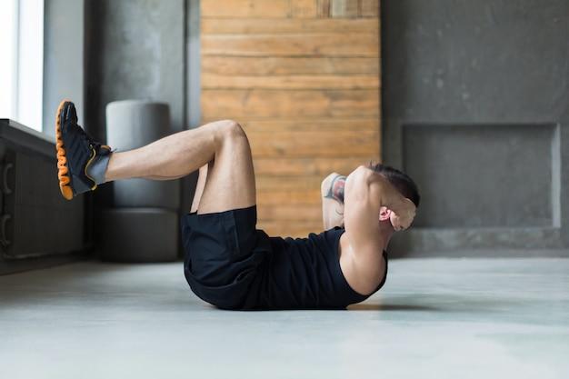 Training des jungen mannes im fitnessclub. profil des kaukasischen kerls, der übung macht, sit-ups und knirschen für bauchmuskeln, training drinnen