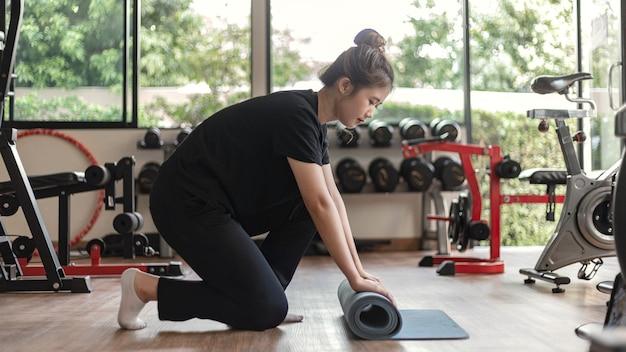 Training-fitnessstudio-konzept ein weiblicher teenager, der ihren arm benutzt, um eine hantel im fitnessstudio nach oben und unten zu heben.
