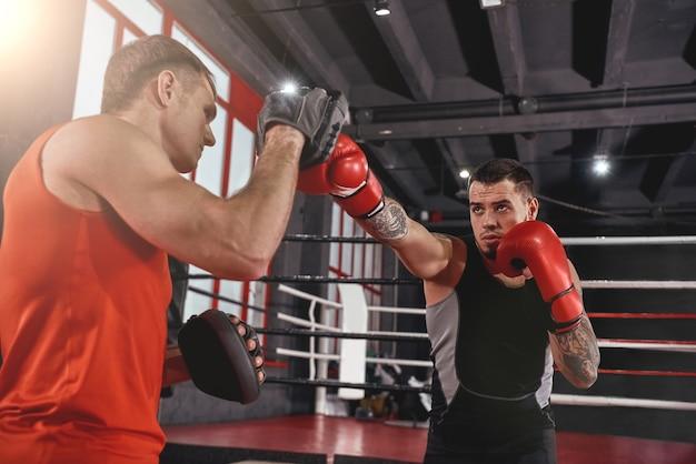 Training für den großen tag. muskulöser athletischer tätowierter mann in sportbekleidung trainiert auf boxpfoten mit partner in black boxing gym