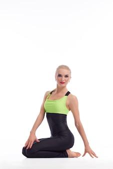 Training für neue höhen. vertikales porträt einer schönen blonden sportlerin mit roten lippen, die in die kamera lächelt, die anmutig sitzt und sportkleidung isoliert auf weiß trägt