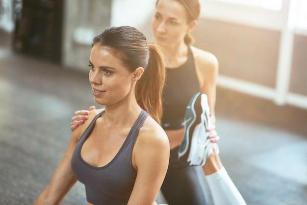 Training mit fitnesstrainer. junge schöne kaukasische frau macht dehnübungen mit hilfe ihres personal trainers im fitnessstudio. sport und gesundes lifestyle-konzept