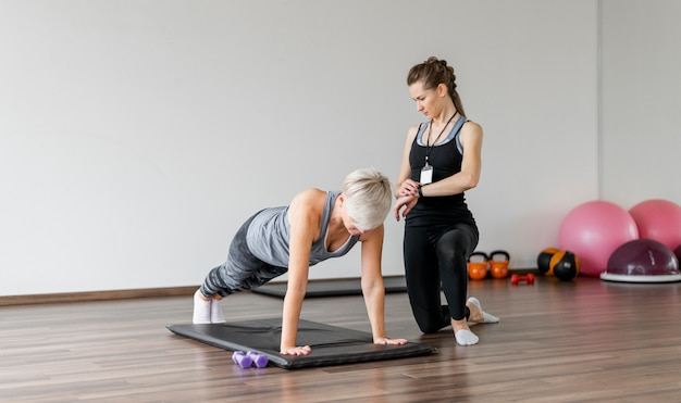 Training mit personal trainer auf yogamatte