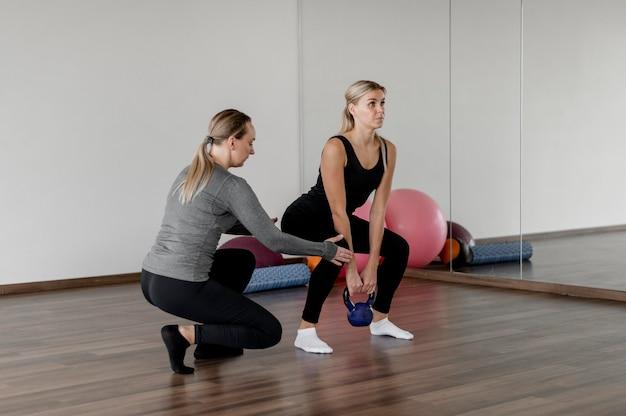 Training mit personal trainer beim kniebeugen