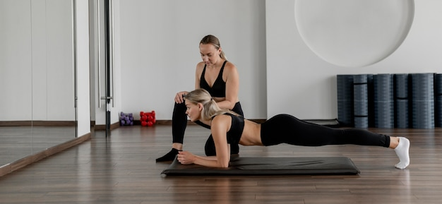 Training mit personal trainer, der planken long shot macht