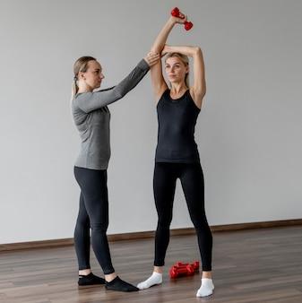 Training mit personal trainer und hanteln