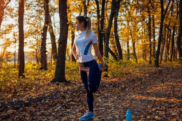 Training und training nach dem lauf im herbst park. frau, die draußen beine ausdehnt. aktiver gesunder lebensstil