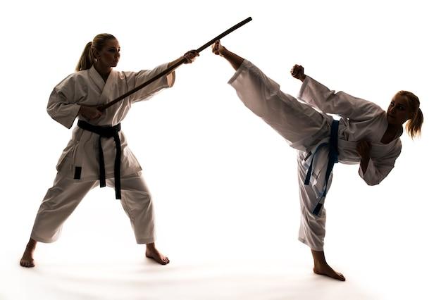Training von zwei mädchen in weißen kimonos mit sportgeräten und karate-stand. auf weißem hintergrund isoliert