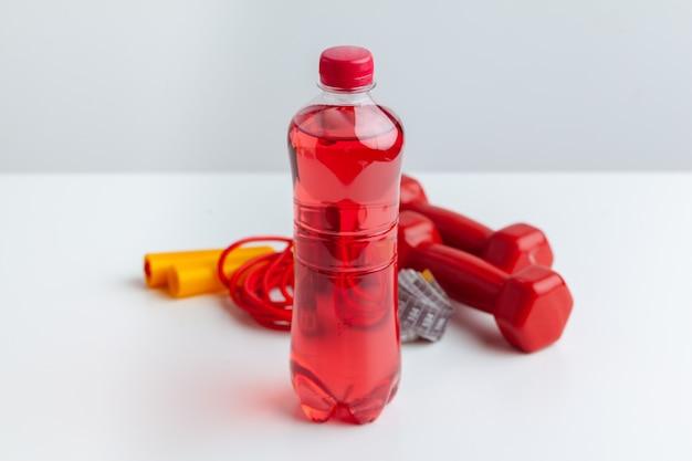Trainings- und erfrischungskonzept. sport und gesundheit. flasche oder frisches wasser in der nähe von springseil