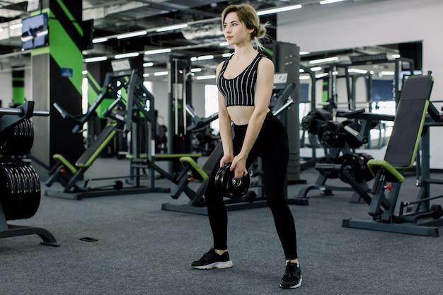 Trainingsbeine im fitnessstudio. attraktive fit frau macht kniebeugen mit pfannkuchen von der bar.