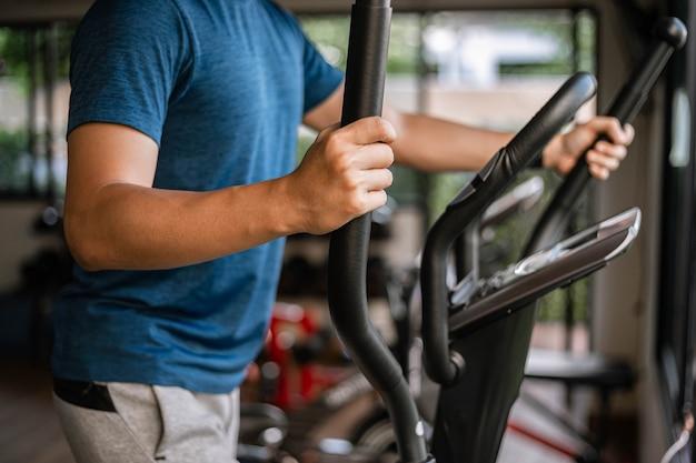 Trainingskonzept für das fitnessstudio ein männlicher teenager, der cardio-training auf dem fahrrad im fitnessstudio als seine gesunde routine macht.