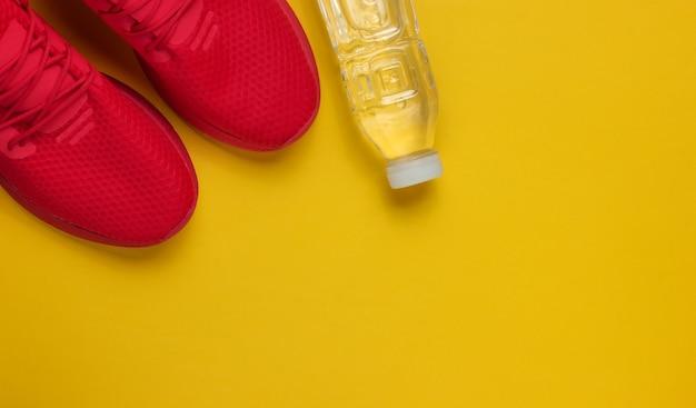 Trainingskonzept. sportschuhe, flaschenwasser auf gelbem hintergrund. flacher laienstil. speicherplatz kopieren