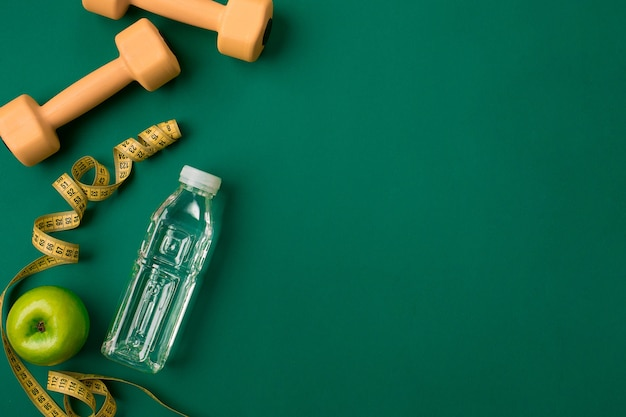 Trainingsplan mit fitnessnahrung und ausrüstung auf grünem hintergrund draufsicht