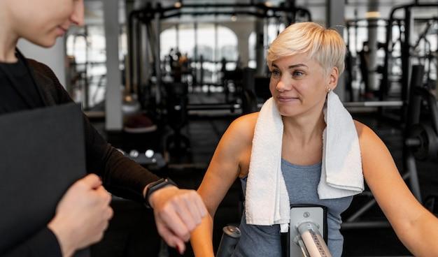 Trainingsprogramm-trainer und klient im fitnessstudio