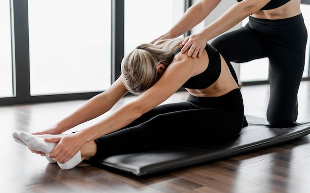Trainingsprogramm-trainer und klient sitzen auf yogamatte