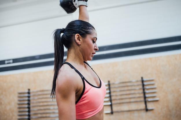 Trainingsschwingkettlebell der jungen frau innen in einer crossfit turnhalle
