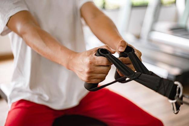 Trainingsstudiokonzept ein männlicher teenager, der ein fitnessstudio verwendet, das seine beiden muskulösen arme gegen die maschine zieht.