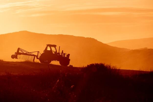 Traktor auf einem bauernhofgebiet bei sonnenuntergang. warme töne der hintergrundbeleuchtung