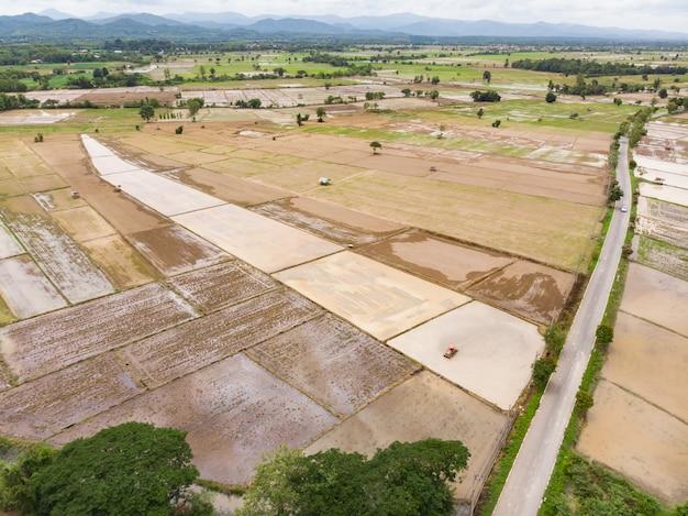 Traktor, der boden in überschwemmtem reisfeld für reispflanze vorbereitet