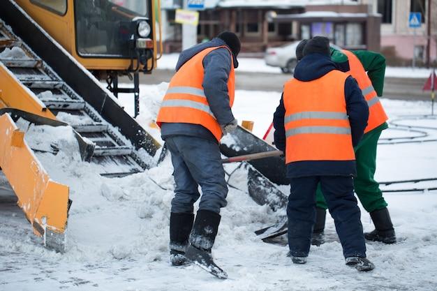 Traktor, der die straße vom schnee reinigt. der bagger reinigt die straßen von großen schneemengen in der stadt. arbeiter fegen im winter schnee von der straße.