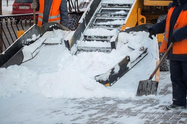 Traktor, der die straße vom schnee säubert. bagger reinigt die straßen von großen schneemengen in der stadt. arbeiter fegen im winter schnee von der straße, reinigen die straße vom schneesturm.