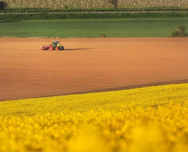 Traktor, der ein feld in südmähren bei sonnenuntergang pflügt