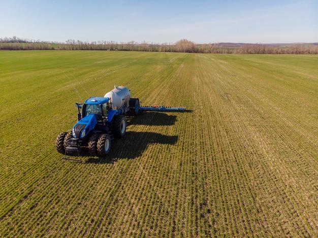 Traktor, der flüssigen mineraldünger auf den boden auf winterweizen aufträgt