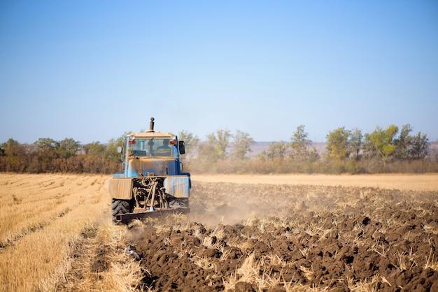 Traktor, der nach der ernte mit blauem himmel am herbsttag direkt in die stoppeln sät.