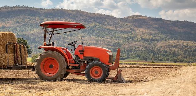 Traktor im landwirtschaftsfeld mit berg und blauem himmel