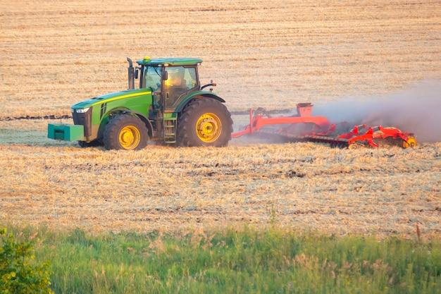 Traktor pflügt das feld nach der ernte