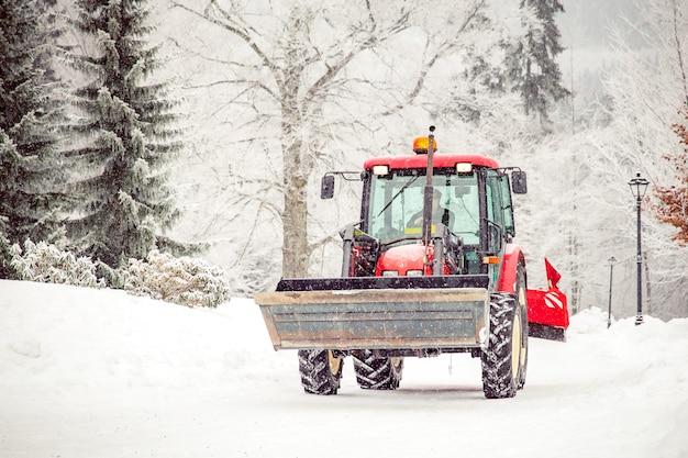 Traktor säubert straße vom schnee im winter