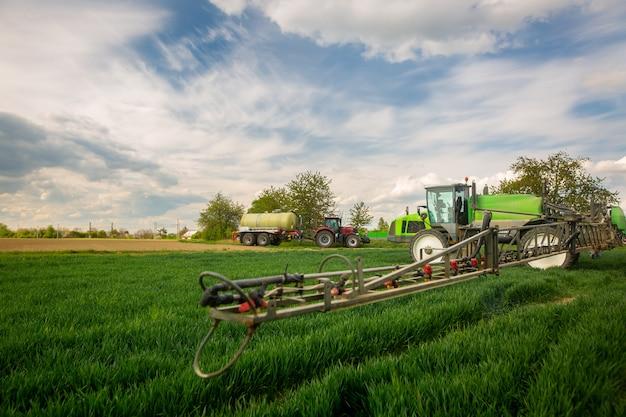 Traktor sprüht pestizide, düngung auf dem gemüsefeld mit sprühgerät im frühjahr, düngungskonzept