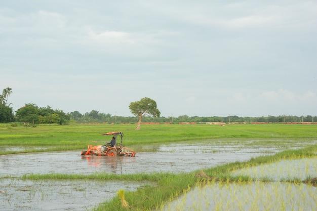 Traktorarbeit pflügt ein feld auf dem bauernhof für das pflanzen