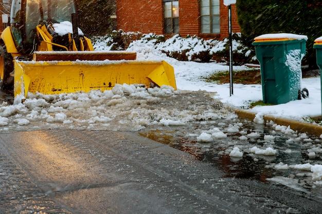 Traktorlader reinigt schnee nach einem schneefall