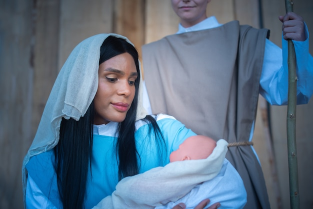 Transgender-frau, die die jungfrau maria darstellt, die das jesuskind umarmt