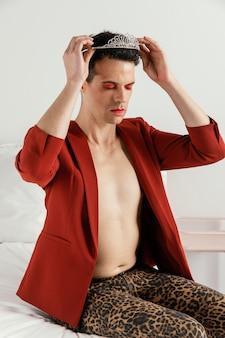 Transgender-person, die rote jacke und eine krone trägt