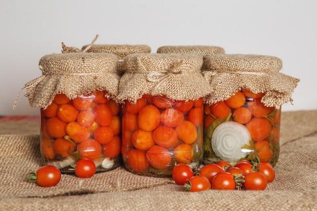 Transparente bänke mit marinierten kirschtomaten. hauskonserven. banken eingelegte tomaten