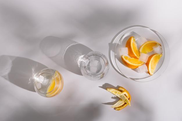 Transparente gläser mit erfrischendem kaltem wasser mit zitronen- und eisscheiben natürliches licht und harte schatten