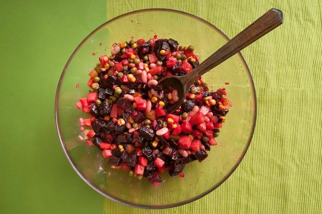Transparente glasschale mit vinaigrette. salat aus einer mischung aus rohem und gekochtem gemüse. vegetarisches essen.