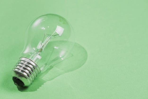 Transparente glühbirne auf grünem hintergrund