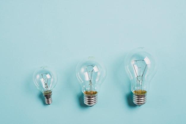 Transparente glühlampe auf blauem hintergrund aufwachsen