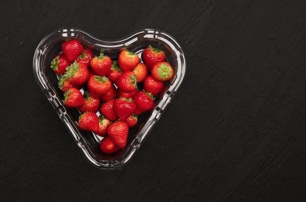 Transparente kunststoffschale mit frisch gepflückten erdbeeren, isoliert auf schwarz