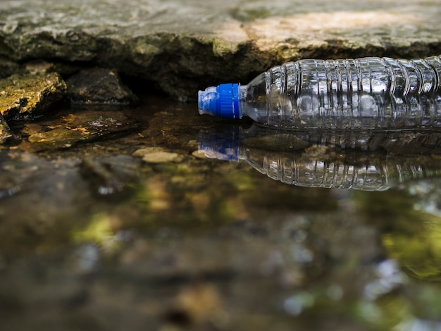 Transparente leere plastikwasserflasche, die auf wasser schwimmt