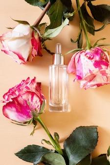 Transparente modellflasche aus glas mit tropfer zwischen rosa und weißen rosenblüten