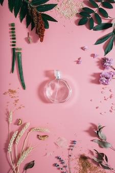 Transparente parfümflasche in blumen auf rosa wand. frühlingswand mit aroma-parfüm. flach liegen