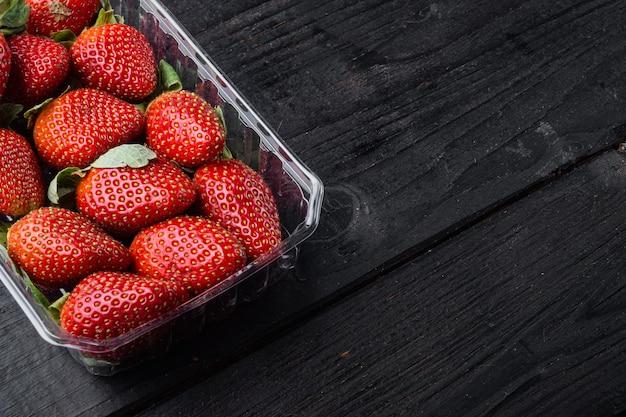 Transparente plastikschale mit frisch gepflückten erdbeeren